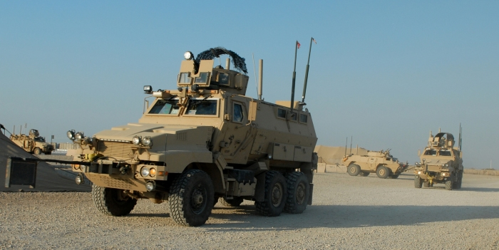 U.S. Soldiers assigned to Delta Company, 1st Battalion, 186th Infantry Regiment, 41st Infantry Brigade Combat Team, head out for a mission aboard Caiman mine-resistant, ambush-protected vehicles and an M1117 Guardian armored security vehicle, background, at Camp Adder, Iraq, Oct. 31, 2009. (U.S. Army photo by Spc. Anita VanderMolen/Released)